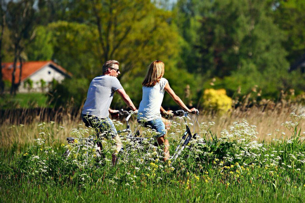 Ein Paar fährt Fahhrad durch die blühende Natur